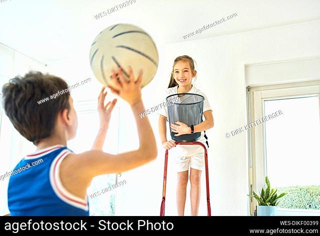 Boy and girl playing basketball at home