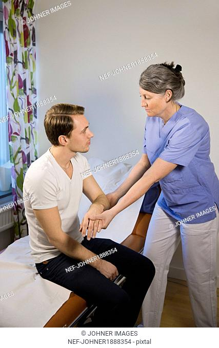 Doctor checking patients arm