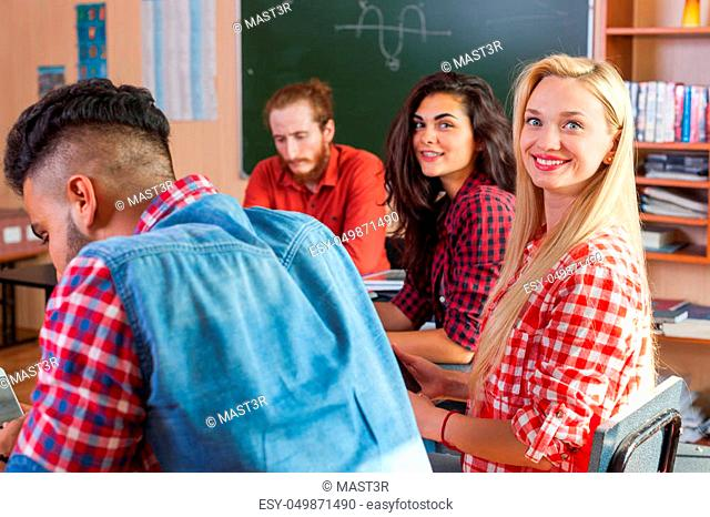 Mixed Race Students Group With Professor Sit Desk University Classroom, Two Beautiful Young Girls Wear Checked Shirt Looking Camera Happy Smiling