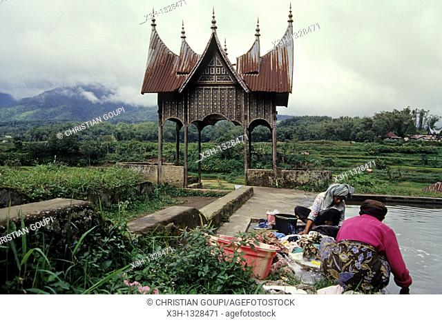 women doing the washing, traditional roof shapes of the Minangkabau houses, Padang region, Sumatra island, Republic of Indonesia, Southeast Asia and Oceania