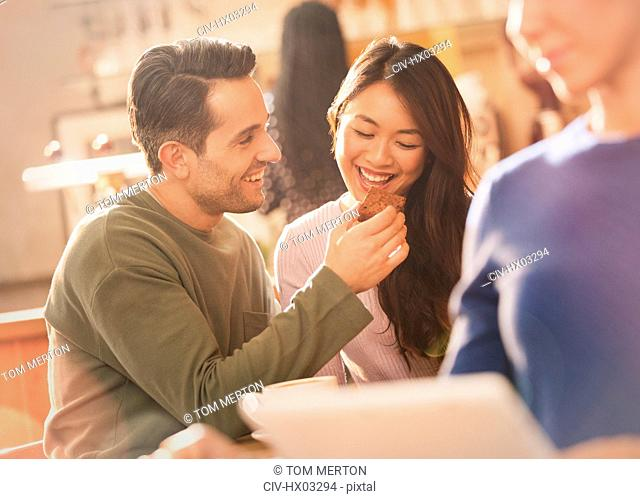 Boyfriend feeding brownie to girlfriend at cafe