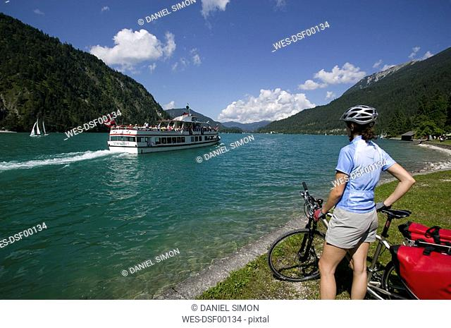 Austria, Tyrol, Achensee, Woman with mountainbike watching out on lakeshore
