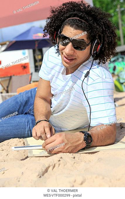 Portrait of a young man with digital tablet listening music on the beach