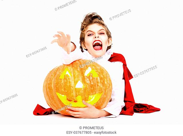 Cool teen boy in a costume of vampire posing with pumpkin with different emotions. Halloween