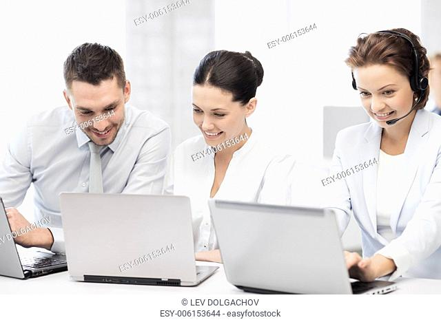 picture of group of people working with laptops in office