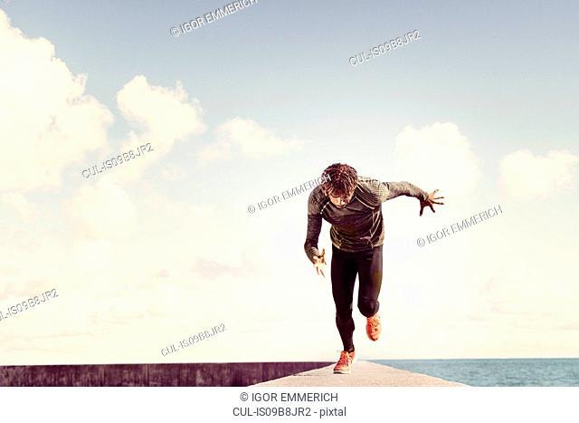 Young man running along sea wall, front view