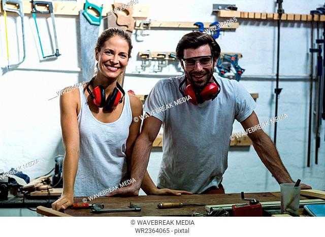 Male and female carpenters standing together in workshop
