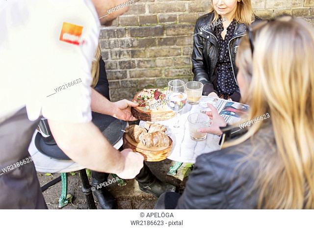 Waiter serving food to customers at sidewalk cafe