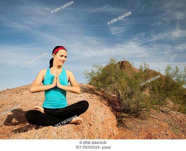 USA, Arizona, Phoenix, Young woman practicing yoga on desert