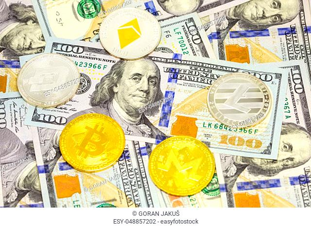Cryptocurrency bitcoin, dash, litecoin, ethereum, monerocoins displayed on a heap of one hundred dollar bills