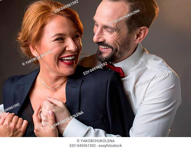 Portrait of joyful loving mature couple hugging and laughing. Caring gentleman is giving his jacket to lady with fondness. Isolated