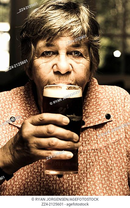 Dark photograph of an adorable senior woman enjoying a pint of cold dark beer inside bowls club. Social seniors