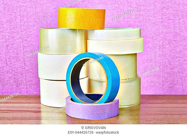 Set of transparent duct tape and colored masking paper tape on purple background