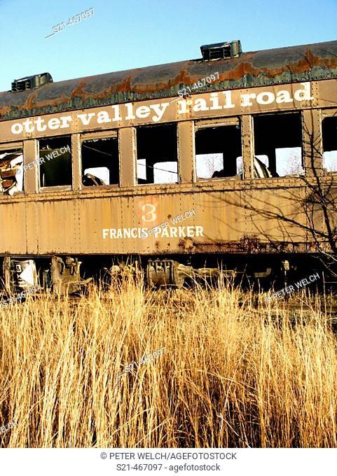 A decaying railroad car is photographed on a bright November day