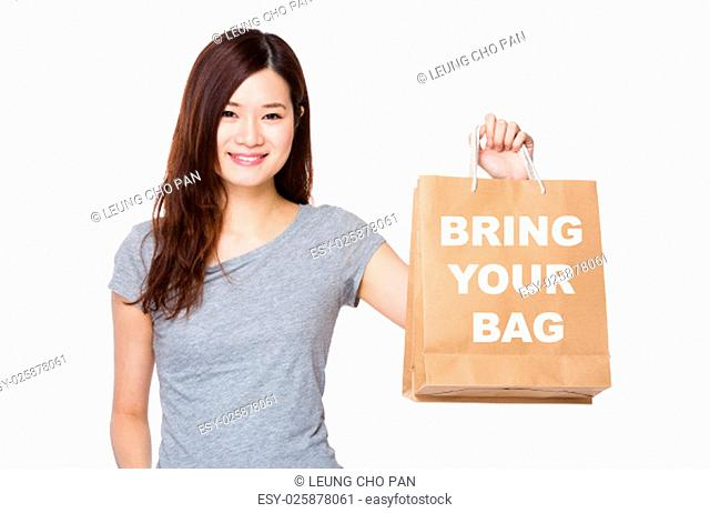 Asian Woman hold with shopping bag for showing phrase of bring your bag