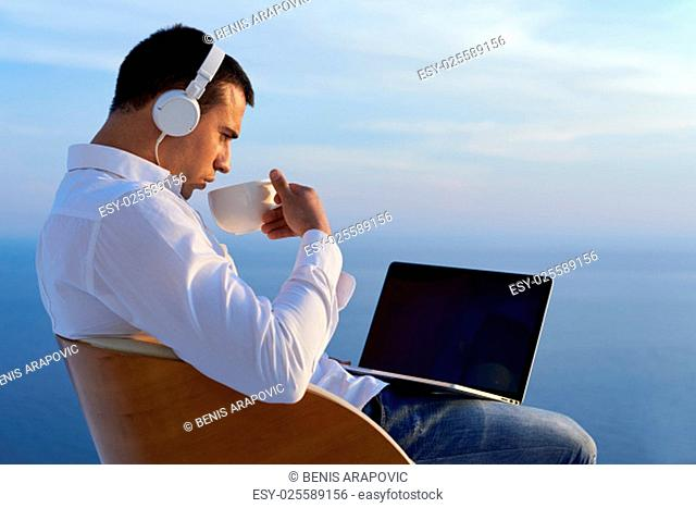 handsome young man relaxing and working on laptop computer at home balcony while looking sunset