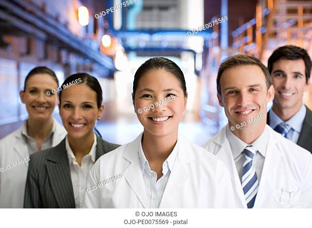 Business people and scientists standing together in factory