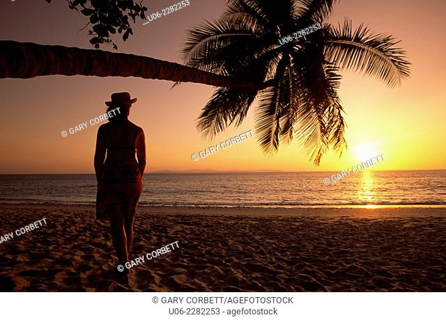 Punta Leona beach on the Pacific coast of Costa Rica showing palm trees and surf, a sunset and a woman watching the sunset