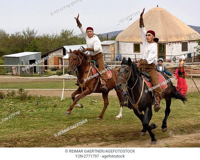 Kazakh horse riders galloping past with arms raised in Huns Village Kazakhstan