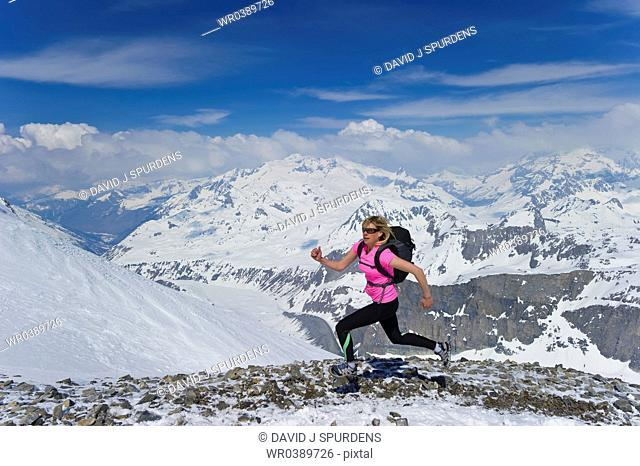 A woman running fast across snowy mountains