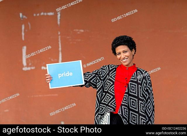 Italy, Tuscany, Pistoia, Smiling woman holding sign