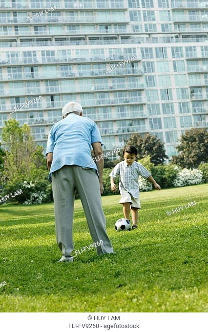 Grandfather and Grandson Playing Soccer in Park, Toronto, Ontario
