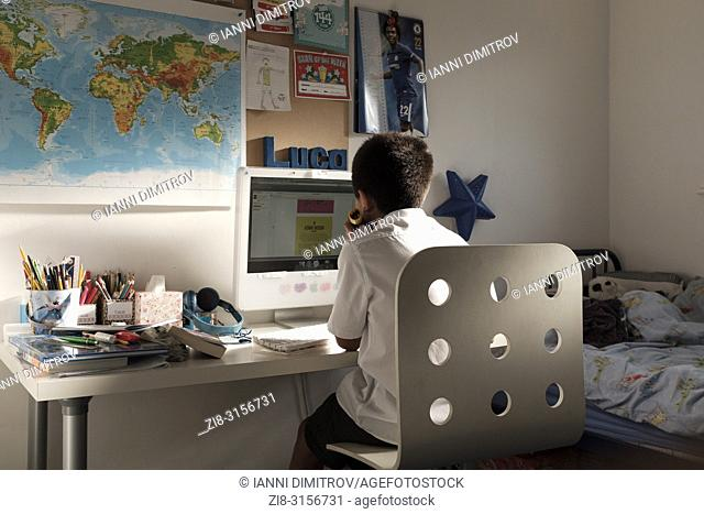UK, Surrey-Schoolboy-11 years old, studies nin his room