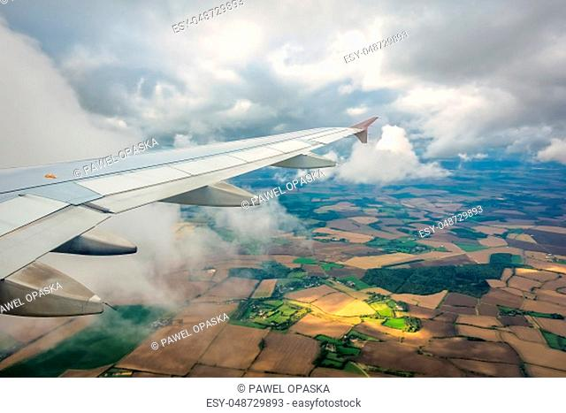 Window view of the wing of an airplane flying above the clouds and english countryside