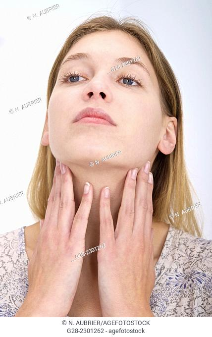 Young woman putting her hands around her throat for thyroid problems