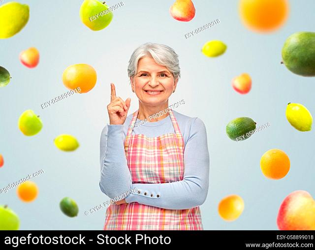 smiling senior woman in apron pointing finger up