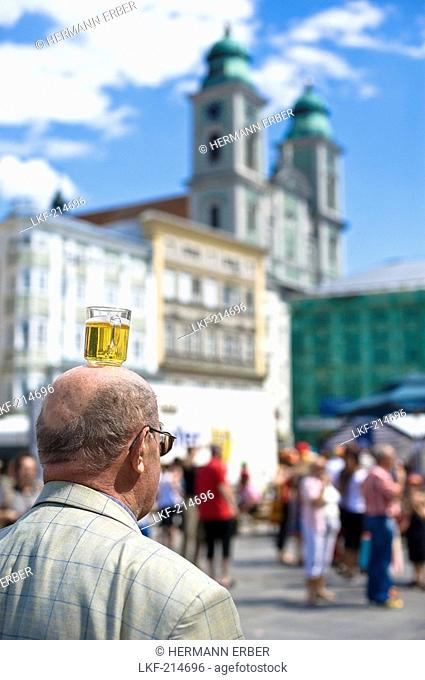 Man balancing a beer mug on his head, dome in the background, Central Square, Linz, Upper Austria, Austria