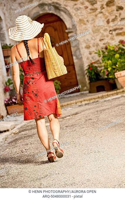 Woman walking with grocery shopping bag over her shoulder through a street at La Palud at the Verdon Gorge in south France