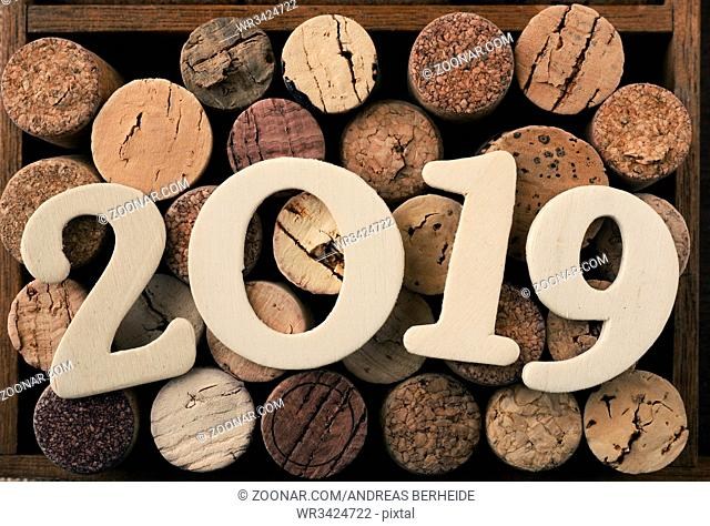 Wooden 2019 on bottle cork in a wooden box, view from above