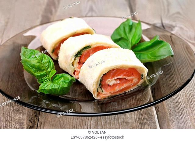 Lavash rolls with salmon and cheese on glas plate, close up view