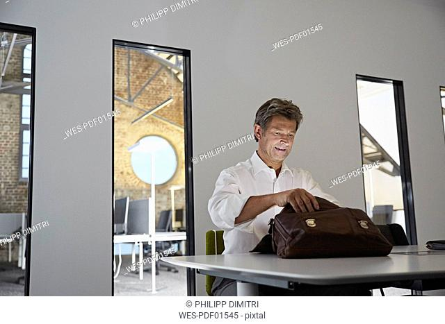 Businessman looking in shining briefcase in conference room of modern office