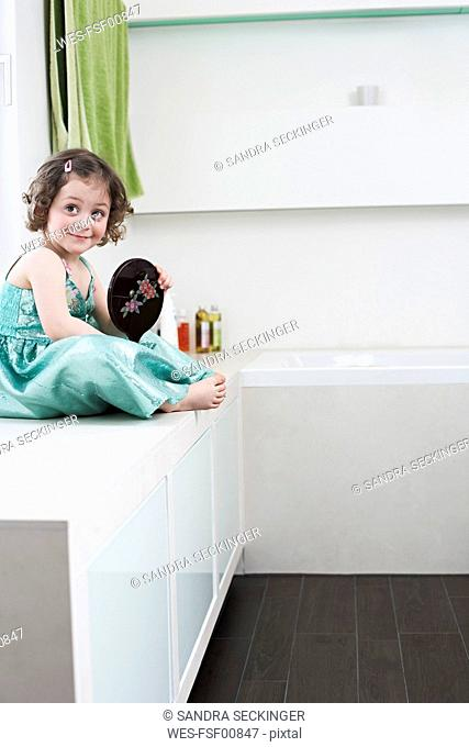 Portrait of smiling little girl with hand mirror sitting in bathroom