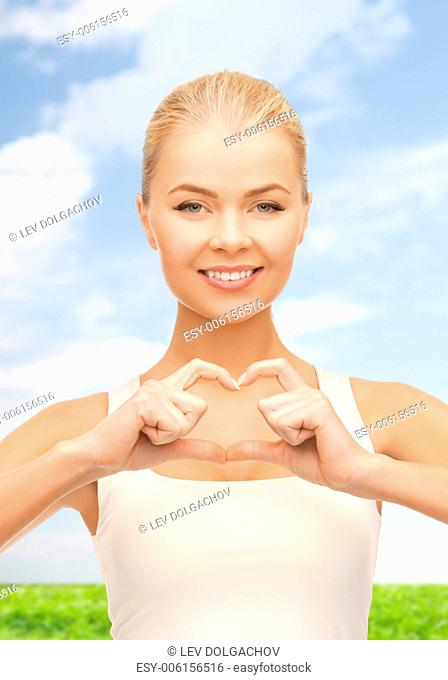 love and gesture concept - smiling woman showing heart shape gesture
