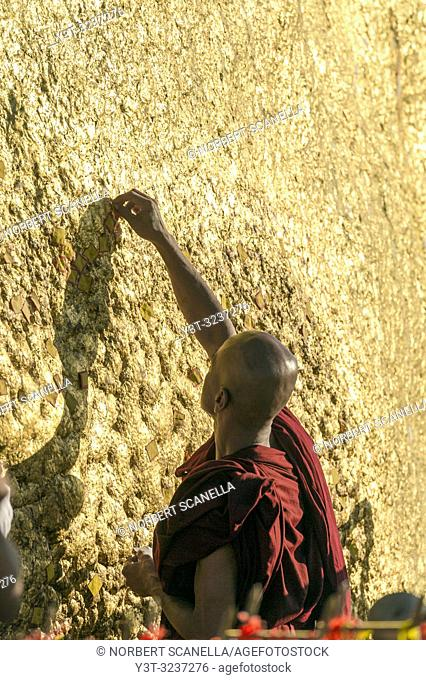 Myanmar (formerly Burma). Kyaiktiyo. State Mon. Sacred site of the golden rock. Monk depositing gold leaves