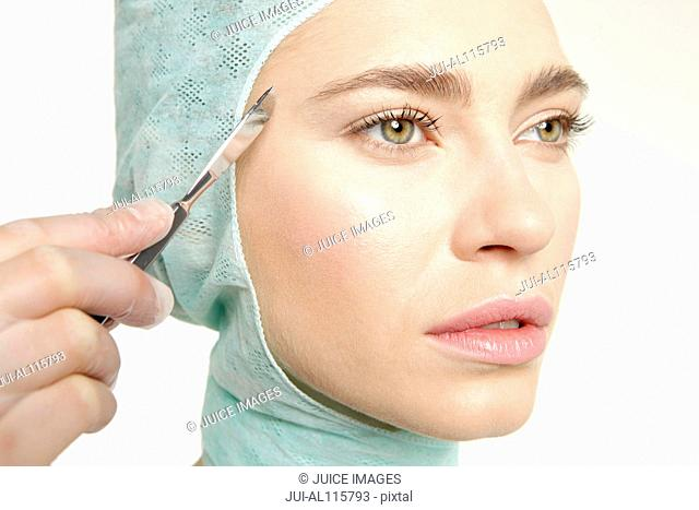 Young woman undergoing plastic surgery with scalpel