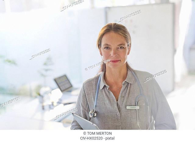 Portrait confident female doctor with digital tablet in doctor's office