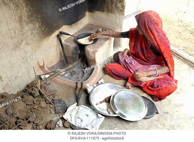 A  woman making wheat bread or rotis  on a fireplace by taking child in lap ; Rajasthan ; India