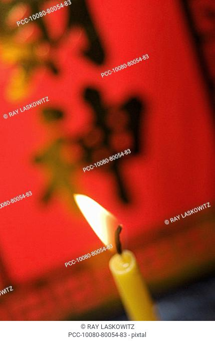 Close-up of lit candles, red poster asian characters on it blurred in background