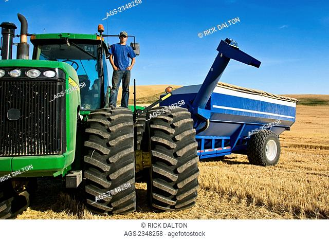 Agriculture - A young farmer atop his tractor during a short break from harvest in the Palouse region / near Pullman, Washington, USA