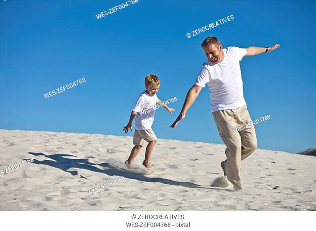 Playful father and son in sand