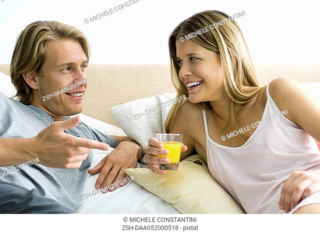 Couple talking together in bed, woman holding glass of orange juice