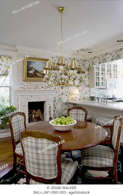EATING AREAS: Round table off kitchen, plaid upholstered French provincial chairs, chandelier with gold shades, small white brick fireplace converted to gas