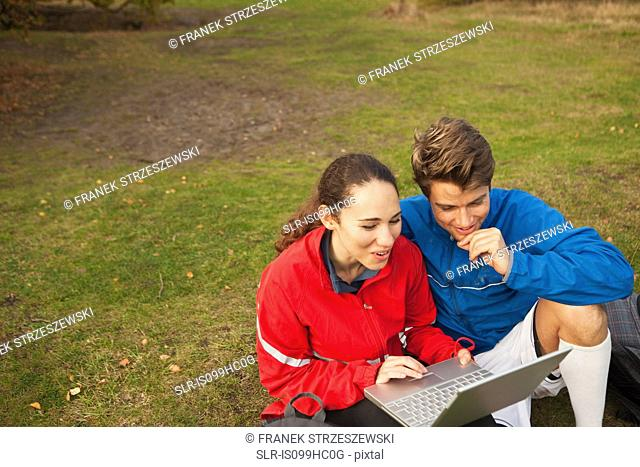 Young couple using laptop in park