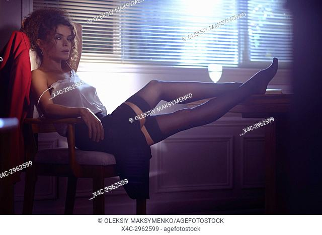 Artistic sensual portrait of a beautiful sexy woman sitting in a chair half undressed in dim night light coming from the window with her legs in stockings on a...