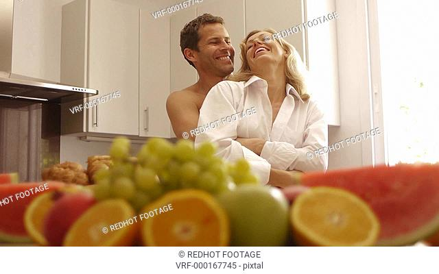 Medium dolly shot of happy couple in kitchen together, Marbella region, Spain