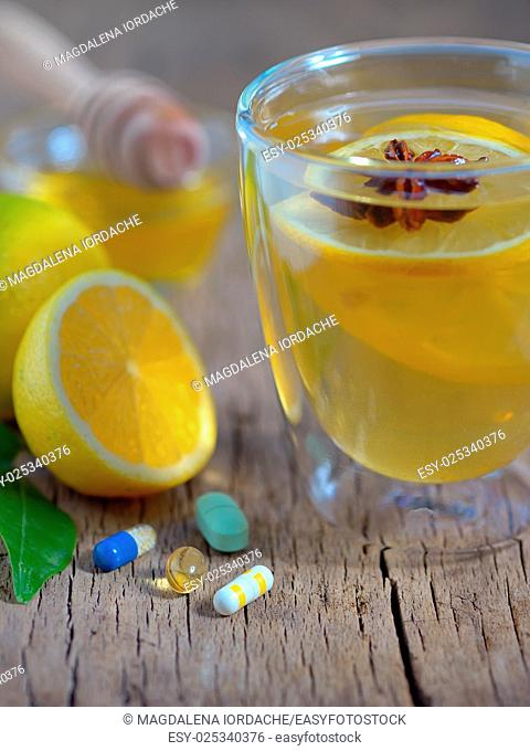 Hot lemon tea and pills on wooden table